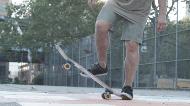 slow motion shot of a skateboarder on a hot summer day - 柵点の映像素材/bロール