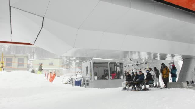 スキーリフトチェアのスローモーションショットは、冬の曇りの日にコロラド州ボルダー近くのエルドラスキーリゾートで山の頂上にそれらを取るためにスキーヤーとスノーボーダーの小さ� - ゲレンデ点の映像素材/bロール