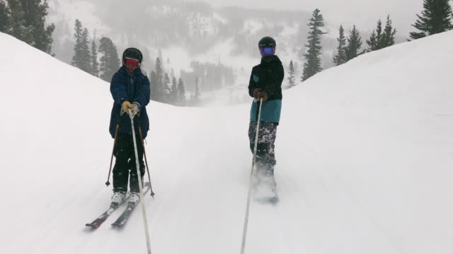 slow motion shot of a skier and a snowboarder being pulled behind a snowmobile at eldora ski resort near boulder, colorado on a snowy, overcast, winter day - ski holiday stock videos & royalty-free footage