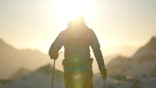 slow motion shot of a skier crossing a snow field with sun behind - warm clothing stock videos & royalty-free footage