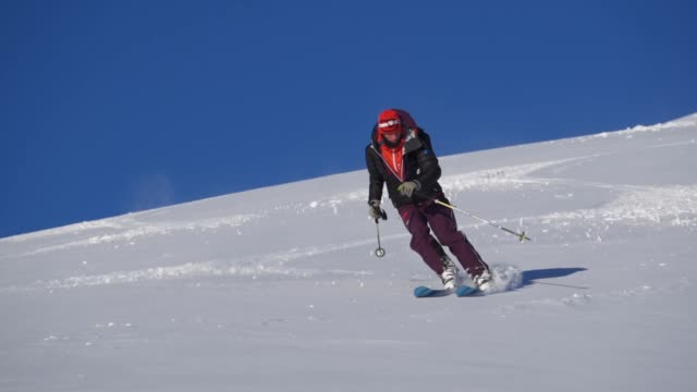stockvideo's en b-roll-footage met slow motion shot van een skiër afdalen een berg - ski jack