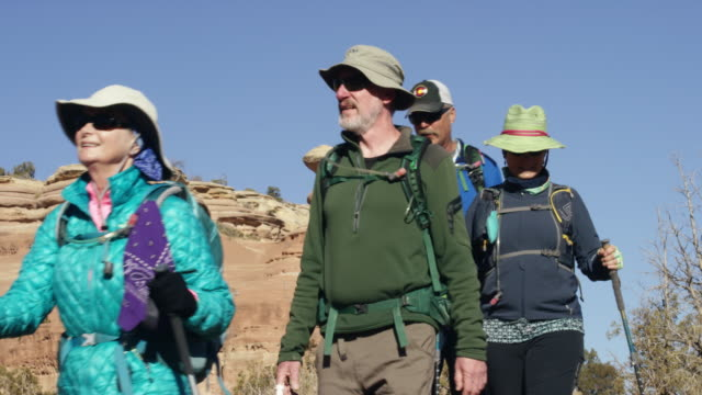 slow motion shot of a small group of mature caucasian men and women hiking together in the rocky high desert mountains of western colorado on a clear, sunny day - tourism stock videos & royalty-free footage