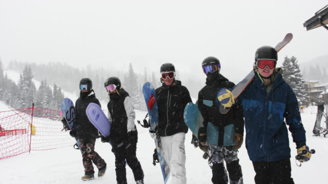 slow motion shot of a small group of skiers and snowboarders in full winter gear talking, smiling, and walking together toward a ski lift at eldora ski resort near boulder, colorado on a snowy, overcast day in winter - snowboarding stock videos & royalty-free footage