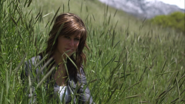 Slow motion shot of a smiling young woman seated in tall grass.