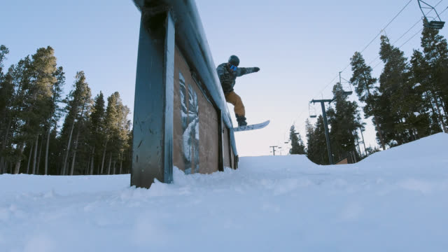 """slow motion shot of a snowboarder in full winter gear completing a """"board slide switchup"""" trick on stunt rails with a forest and a ski jump in the background at eldora ski resort near boulder, colorado on a bright, sunny, winter - ski holiday stock videos & royalty-free footage"""