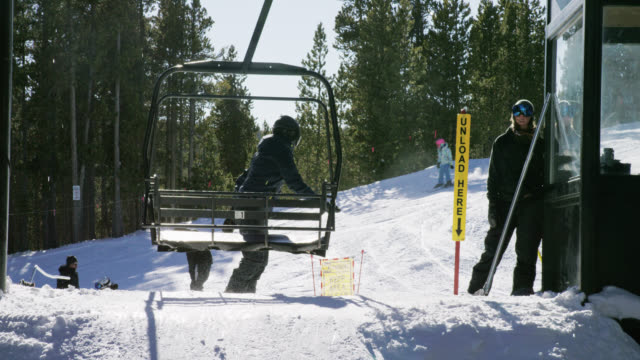 slow motion shot of a snowboarder in full winter gear exiting the ski lift at eldora ski resort near boulder, colorado on a bright, sunny day in winter - ski holiday stock videos & royalty-free footage