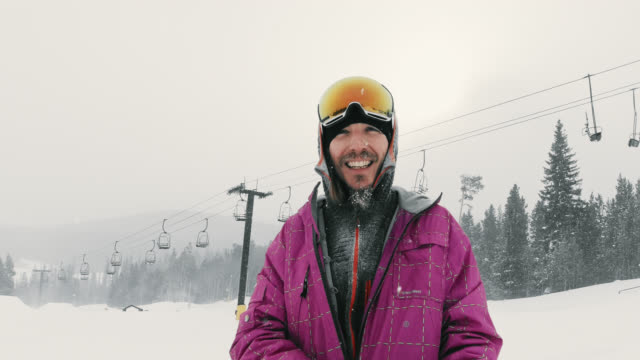 slow motion shot of a snowboarder in his thirties wearing full winter gear and goggles smiling and talks to the camera with a ski lift behind him at eldora ski resort near boulder, colorado on a snowy, overcast day - ski goggles stock videos & royalty-free footage