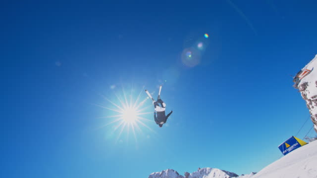 Slow motion shot of a snowboarder making a somersault while jumping over the kicker in the snowpark Also available
