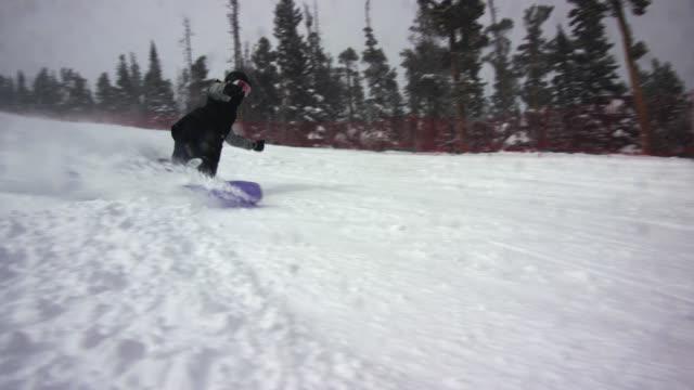 雪の上にコロラド州ボルダー近くのエルドラスキーリゾートの森に囲まれたカメラで、スキーランで完全な冬のギアを彫り、雪を吹き付けるスノーボーダーのスローモーションショット - ゲレンデ点の映像素材/bロール