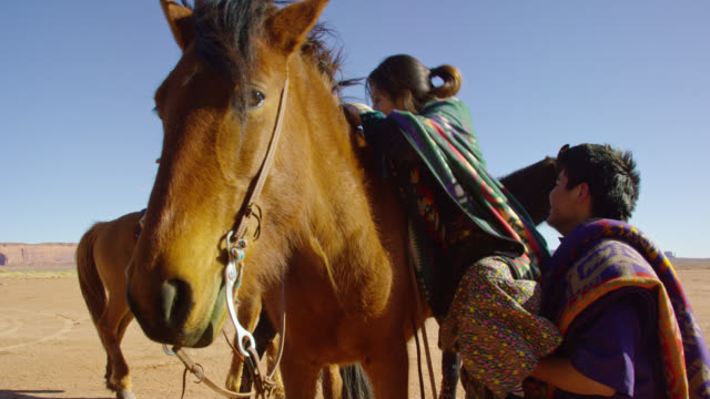 slow motion shot of a teenaged native american boy helping a teenaged girl wearing a traditional navajo blanket on to her horse while riding in the monument valley desert on a clear, bright day - traditional clothing stock videos & royalty-free footage