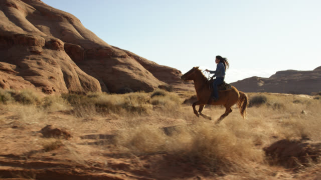 slow motion shot of a teenaged native american girl (navajo) galloping on her horse through the monument valley desert in arizona/utah on a sunny afternoon - all horse riding stock videos & royalty-free footage