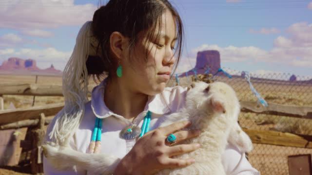 アリゾナ州モニュメントバレーで顔の近くで子羊を抱いた10代のネイティブアメリカンの女の子のスローモーションショット(大きな岩の形成を背景に) - 羊飼い点の映像素材/bロール