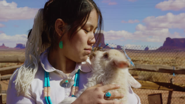 slow motion shot of a teenaged native american girl holding a lamb close to her face in monument valley, arizona/utah on a sunny day with large rock formations in the background - navajo culture stock videos & royalty-free footage