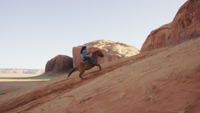 slow motion shot of a teenaged native american girl (navajo) riding her horse up a steep, sandy hill in the monument valley desert in arizona/utah at sunset next to a large rock formation - minority groups stock videos & royalty-free footage