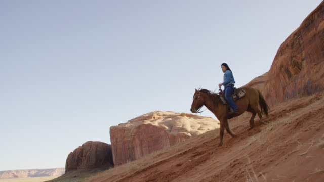 vidéos et rushes de slow motion shot of a teenaged native american girl (navajo) riding her horse down a steep hill with her dog in the monument valley desert in arizona/utah at sunset next to a large rock formation - hill
