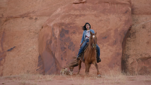 vidéos et rushes de slow motion shot of a teenaged native american girl (navajo) riding her horse down a steep hill with her pet dogs in the monument valley desert in arizona/utah at sunset next to a large rock formation - hill