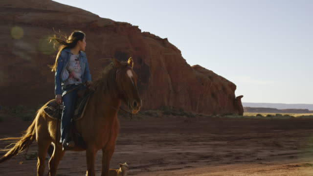 slow motion shot of a teenaged native american girl (navajo) sitting on her horse and looking over the landscape of the monument valley desert in arizona/utah at sunset next to a large rock formation - indigenous peoples of the americas stock videos & royalty-free footage