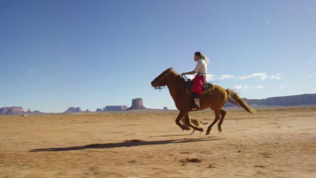 slow motion shot of a teenaged native american girl wearing traditional navajo clothing galloping on her horse across the monument valley desert with her pet dogs with large rock formations in the distance on a clear, bright day - gallop animal gait stock videos & royalty-free footage