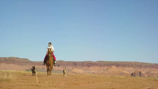 vídeos de stock, filmes e b-roll de tiro em câmera lenta de uma adolescente nativa americana vestindo roupas tradicionais navajo montando seu cavalo através do deserto do vale monumento com seus cães de estimação com grandes formações rochosas à distância em um dia claro e brilhante - pet clothing