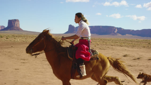 vídeos de stock e filmes b-roll de slow motion shot of a teenaged native american girl wearing traditional navajo clothing galloping on her horse across the monument valley desert with her pet dogs with large rock formations in the distance on a clear, bright day - cultura tribal da américa do norte