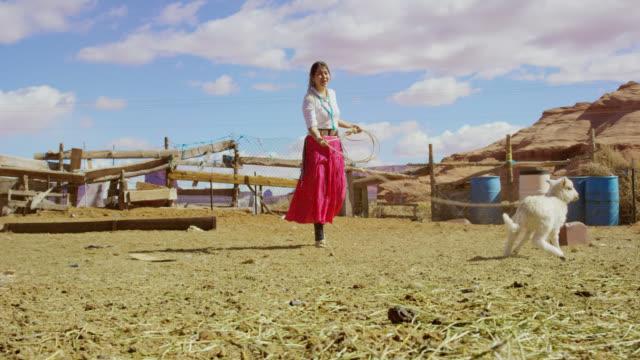 伝統的なナバホ服を着た10代のネイティブアメリカンの女の子のスローモーションショットローピング/牧草地でフェンスで子羊を投げ捨てる羊は、大きな岩の形成を背景にした晴れた日にア� - 羊飼い点の映像素材/bロール