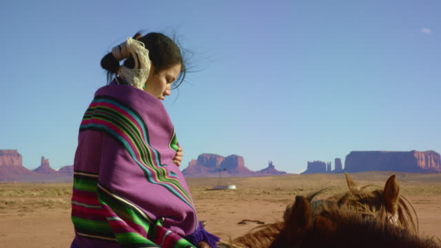 slow motion shot of a teenaged native american girl wearing wrapped up in a traditional navajo blanket sits on her horse in the monument valley desert with large rock formations in the distance on a clear, bright day - indigenous peoples of the americas stock videos & royalty-free footage