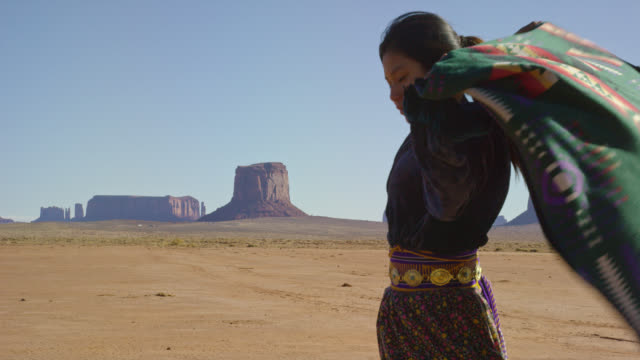 vídeos de stock e filmes b-roll de slow motion shot of a teenaged native american girl wrapping a traditional navajo blanket around her shoulders in the monument valley desert with large rock formations in the distance on a clear, bright day - cultura tribal da américa do norte