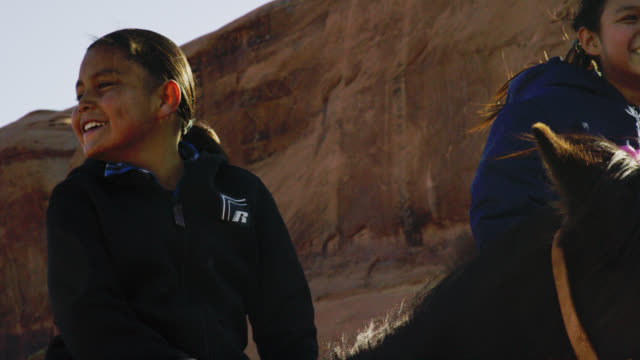 slow motion shot of a ten-year-old native american boy (navajo) smiles and laughs while sitting on his horse next to a teenaged girl in the monument valley desert in arizona/utah on a sunny day next to a large rock formation - horse family stock videos & royalty-free footage