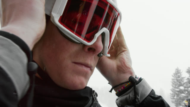 slow motion shot of a twenty-something, male snowboarder putting on his goggles in preparation for snowboarding on a snowy, overcast. winter day - skiwear stock videos & royalty-free footage