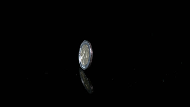 slow motion shot of a two euro cent coin spinning on a reflective surface. - european union coin stock videos & royalty-free footage