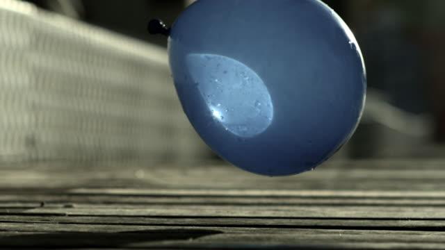 vídeos de stock e filmes b-roll de slow motion shot of a water balloon falling onto a wooden floor. - bomba de água equipamento