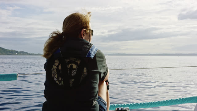 slow motion shot of a woman in her sixties sitting and looking out over puget sound in washington from the deck of a sailboat on a partly cloudy day - mast sailing stock videos & royalty-free footage