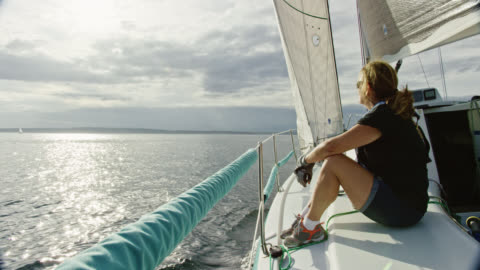 slow motion shot of a woman in her sixties sitting and looking out over puget sound in washington from the deck of a sailboat on a partly cloudy day - sailing boat stock videos & royalty-free footage