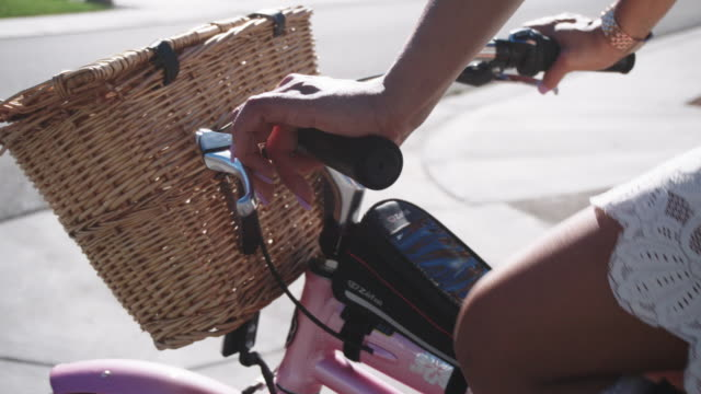 slow motion shot of a woman of mixed race's hands steering a bicycle with a woven basket on the front on a sunny day - woven stock videos & royalty-free footage