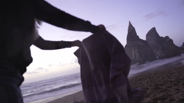 Slow motion shot of a woman shaking out a beach blanket at dusk