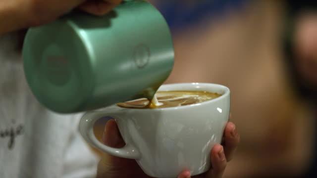 slow motion shot von einer frau hände gießen gedämpfte milch in einen becher voller espresso (kaffee), machen latte kunst in einem coffee shop - kaffeebecher oder teebecher stock-videos und b-roll-filmmaterial