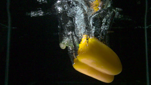 Slow motion shot of a yellow pepper falling into a tank of water.