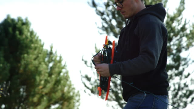 slow motion shot of a young caucasian man in his twenties unstringing christmas lights while decorating for christmas outdoors - hanging stock videos & royalty-free footage