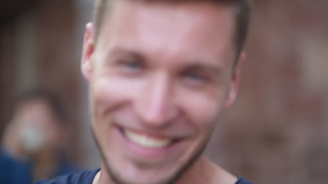 slow motion shot of a young man looking and smiling at camera - vollbart stock-videos und b-roll-filmmaterial