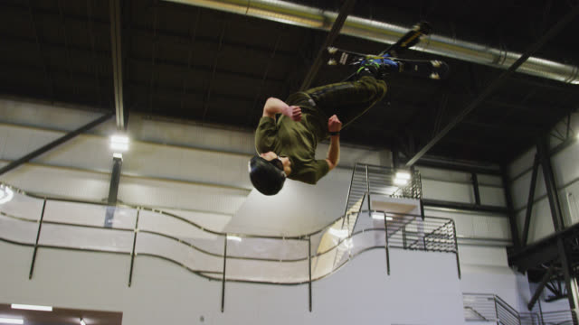 slow motion shot of a young man on roller skis doing a jump trick into a foam pit at an indoor ski ramp practice facility - sporting term stock videos & royalty-free footage