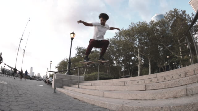 slow motion shot of a young man skateboarding through the streets of new york city - extreme sports点の映像素材/bロール