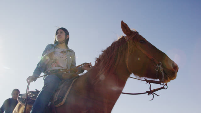 vídeos de stock e filmes b-roll de slow motion shot of a young native american (navajo) woman riding her horse with a small boy behind her on a clear, bright day - cultura tribal da américa do norte