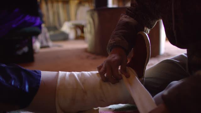 60代の祖母がホーガン(ナバホ小屋)で屋内で見ている間、伝統的なナバホレギンスで女性の足を包む若いネイティブアメリカンの女性のスローモーションショット - インディアン居留地点の映像素材/bロール