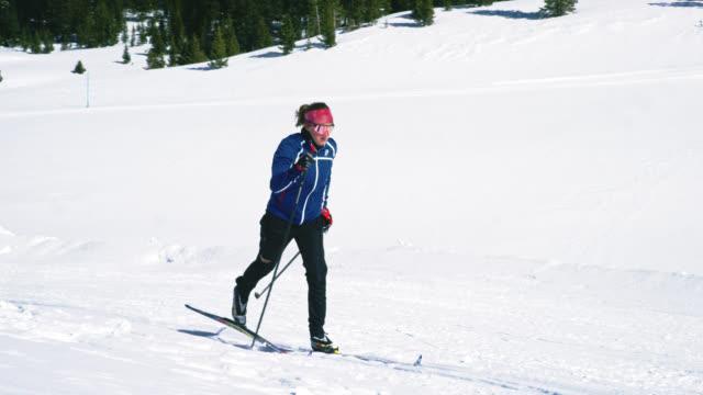 slow motion shot av en ung kvinna i tjugoårsåldern längdskidåkning i bergen på en solig, vinterdag i colorado - längd bildbanksvideor och videomaterial från bakom kulisserna