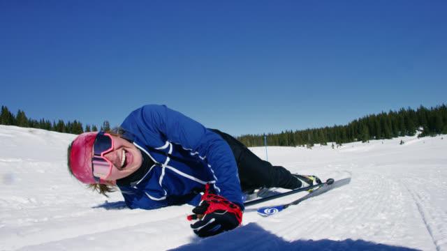 vídeos y material grabado en eventos de stock de disparo a cámara lenta de una mujer joven en sus veinte años esquí de fondo, cayendo sobre la nieve, y riendo mientras mira la cámara - misfortune