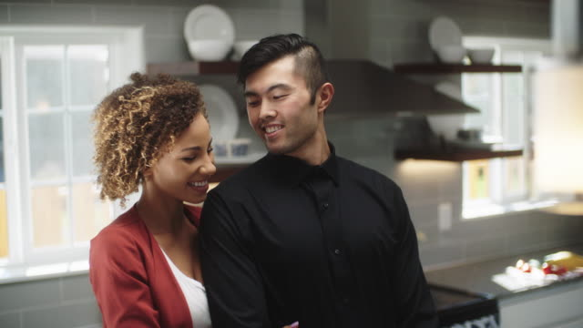 slow motion shot of a young woman of mixed race walking into the room and hugging a young asian man from behind as he works on the counter of a bright, modern kitchen - beautiful woman stock videos & royalty-free footage