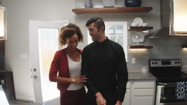 slow motion shot of a young woman of mixed race walking into the room and hugging a young asian man from behind as he slices vegetables with a kitchen knife on the counter as she sits down across from him at island of a bright, modern kitchen - ehemann stock-videos und b-roll-filmmaterial