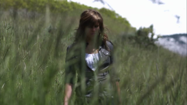 Slow motion shot of a young woman sitting down in tall grass.