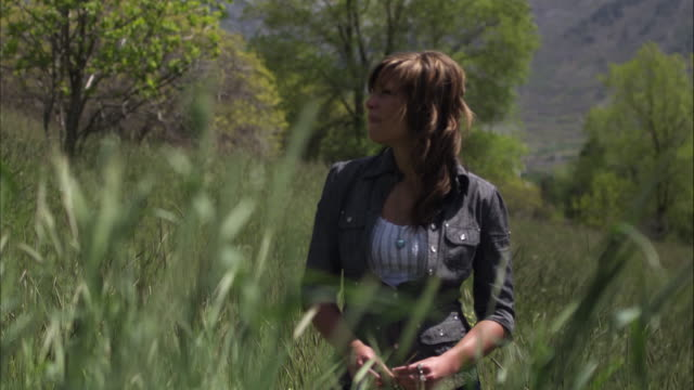 Slow motion shot of a young woman standing in tall grass.
