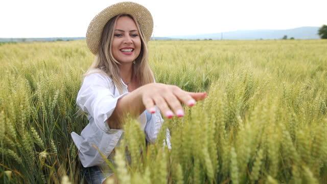 彼女が畑を歩いている間、小麦の作物を愛撫する若い女性の手のスローモーションショット - 穀物 ライムギ点の映像素材/bロール